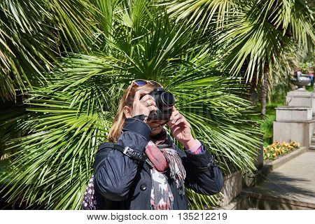 Woman Tourist Photographs Attractions In Park