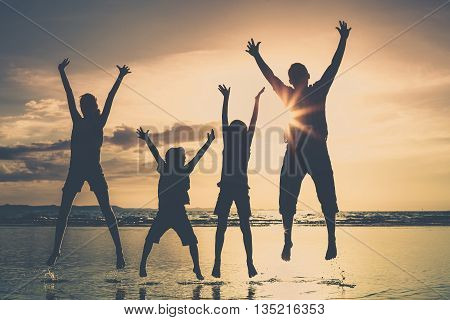 Father and children playing on the beach at the sunset time. Family having fun on the sea. Concept of friendly family and of summer vacation.