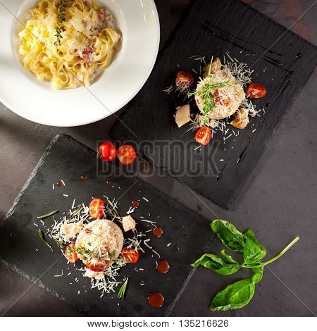 Italian Main Course. Pasta and Risotto on Black Slate Background