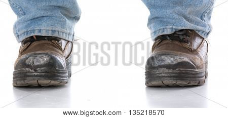 man's legs wearing work boots on white background