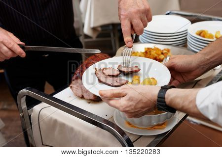 Chef is cutting beefsteak and putting meat to plates