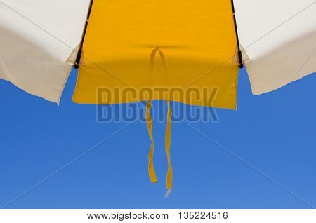 Detail of a beach umbrella with lace on the bottom of the blue sky