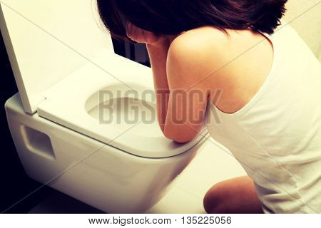 Woman vomiting in toilet.
