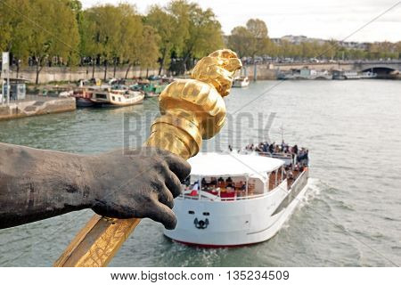 Alexandre III bridge, the torchbearer and tourist boat (Paris, France) Alexandre III bridge between culture and tourism
