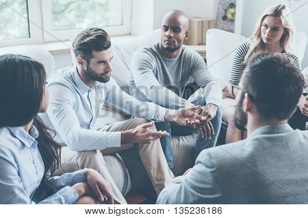 Sharing his problems with group. Group of young people sitting in circle while one man telling something and gesturing