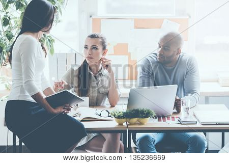 Making decisions together. Three young business people in smart casual wear discussing something while sitting at the office desk together