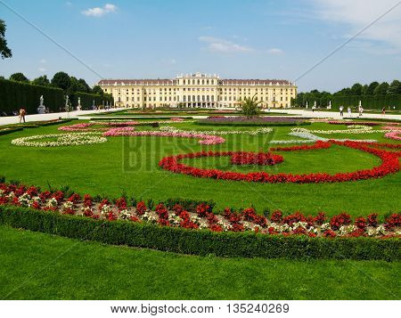 Vienna, Austria - June 17, 2012: People visit the flowering garden in front of the Schonbrunn Palace, the former  Habsburg residence. Palace and Gardens of Schonbrunn are UNESCO World Heritage site.