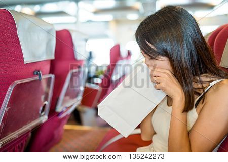 Woman feeling unwell and vomit on paper bag