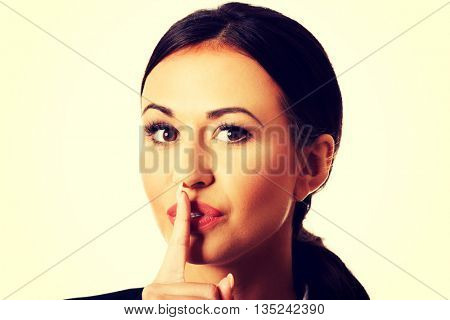 Businesswoman making silent sign
