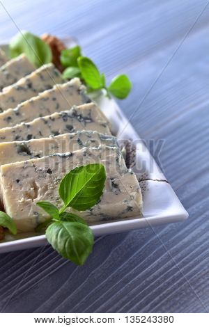 gorgonzola cheese with basil and walnuts on blue table