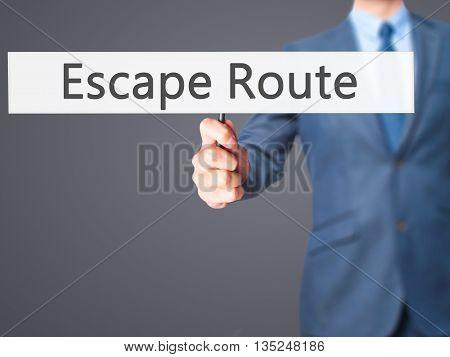 Escape Route - Businessman Hand Holding Sign