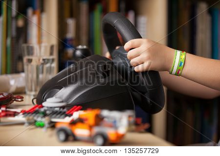 Close up of child's hands holding a computer steering wheel. Future driver. Getting ready for professional driving. Kid's hands driving a car.