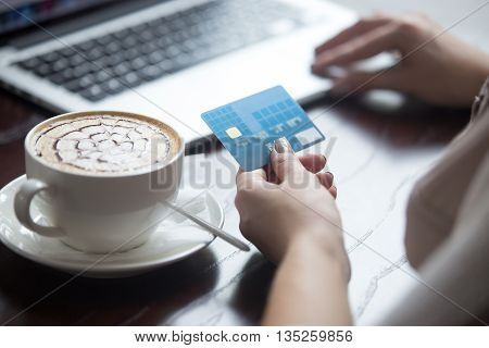 Young beautiful female sitting in modern urban cafe drinking cappuccino and paying with credit card for online shopping on laptop. Back view. Close-up of hands