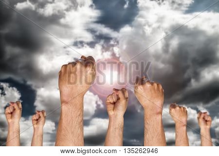 group of human hand showing fist on sky background with the sun, fighting fist concept, fist sign or symbol.