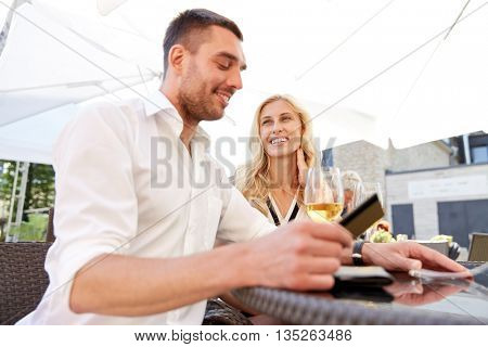 date, people, payment and finances concept - happy couple with credit card and wine glasses paying bill at restaurant