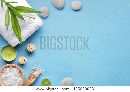 Towel,candle,salt and stone on blue background