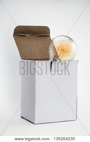 Glowing bulb in white box signifying thinking outside the box concept with room for text on box and white background copy space