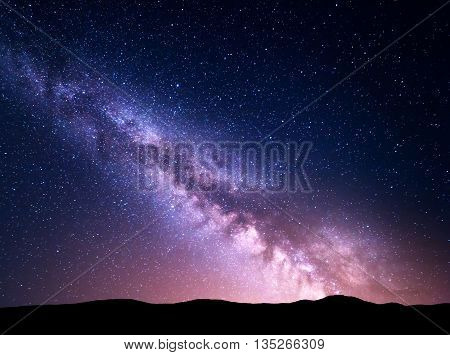 Night landscape with vibrant Milky Way at mountains. Starry sky with hills at summer. Beautiful Universe. Space background. Night sky with Milky Way poster