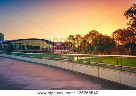 Adelaide, Australia - January 18 2015: Riverbank foot bridge across Torrens River in Adelaide City Business District at sunset South Australia. Color-toning applied