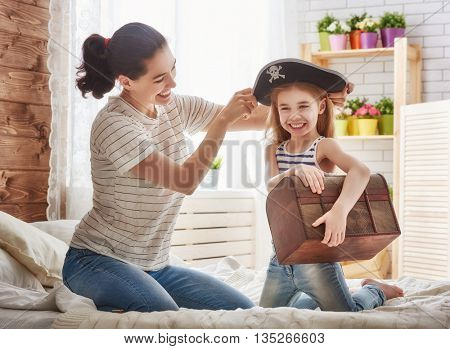 Happy family is preparing for a costume party. Mother and her child girl playing together. Girl in pirate's costume.
