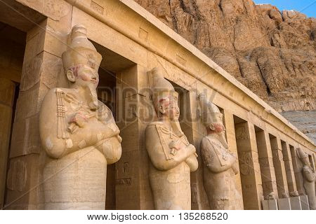 A row of statues of Queen Hatshepsut as Osiris, the god of the dead, at her temple in Luxor, Thebes, Egypt.