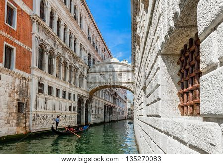 Gondola passing on narrow canal under famous Bridge of Sighs in Venice, Italy.