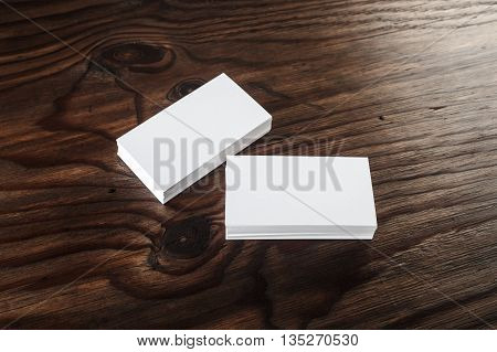 Blank business cards. Blank white business cards on dark wooden table background. Mock-up for branding identity. Blank template for design presentations and portfolios