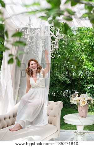 Pretty Woman Having Fun In The Summer Garden Gazebo. Opulent Outdoor Living Area With Flowers For Ce