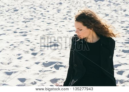 Woman With Curly Brown Hair In A Black Coat Sitting On A Pensive At The Beach On A Sunny Day