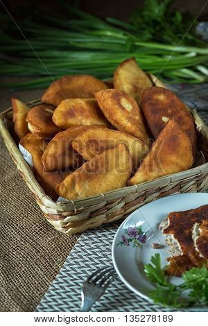 Fried meat pasties on a rustic surface green onion and parsley