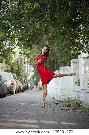 Beautiful ballerina in red dress and in pointe shoes dancing with a book outdoors