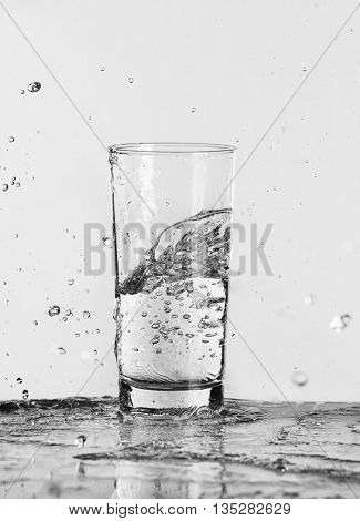 Filled glass of water on light background