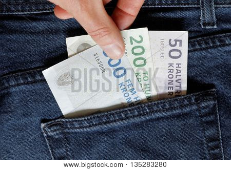 Hand taking Danish bank notes from a jeans pocket