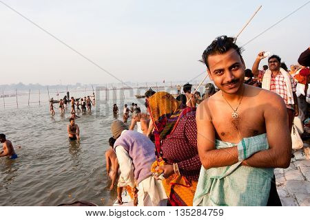 SANGAM, INDIA - JAN 27, 2013: Young indian man smiling after bathe in the confluence of Ganges and Yamuna during the Kumbh Mela on January 27, 2013 in Allahabad, India. In 2013 Mela take 130 mill. people