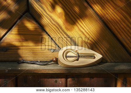 iron jew's-harp in lumber box near wall close up