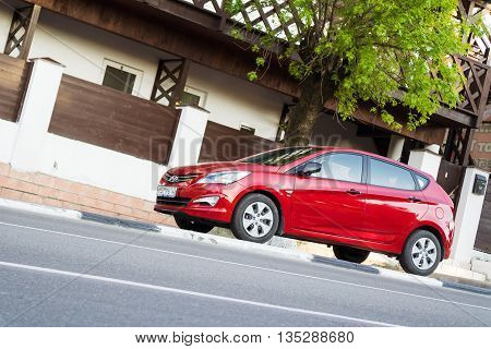 MUNICH GERMANY - APRIL 29 2016: New red Hyundai Solaris parked in the street of Munich. New korean automobile.