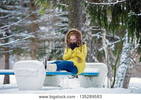 A girl sits on the bench and it is very cold