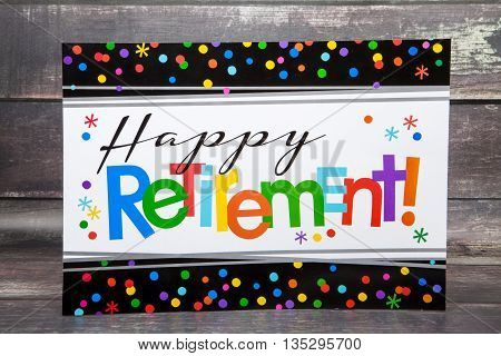 A happy retirement sign against a wood background