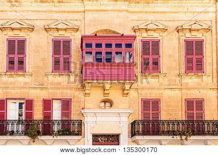 Facade with traditional colorful balcony and shutters, Mdina, Malta