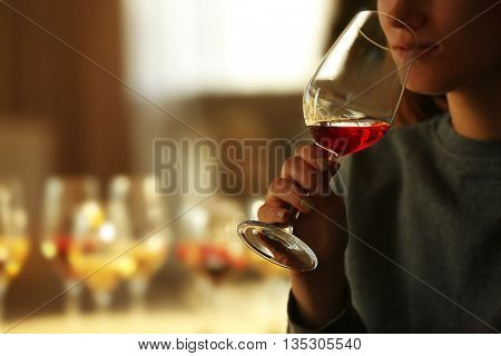 Woman sniffing red wine in a glass, close up