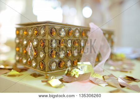 She is on the surface covered with confetti of gold color. The casket is decorated with a large amount of white and yellow jewels.