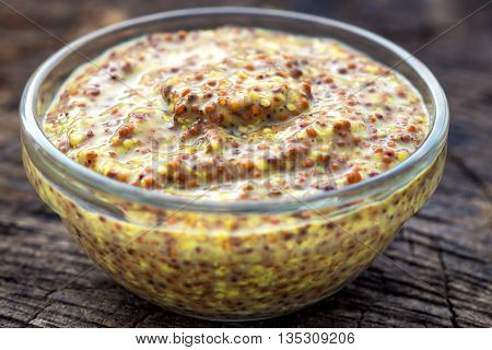 Typical french dijon mustard on wooden background