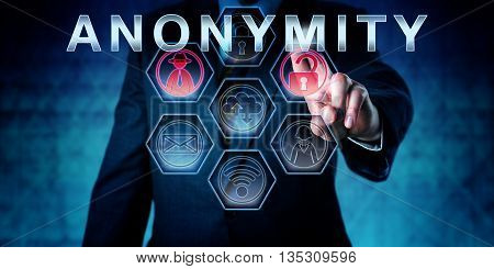 Internet services provider in blue suit is touching ANONYMITY on an interactive virtual control monitor. Business metaphor and information technology concept for anonymous internet access.