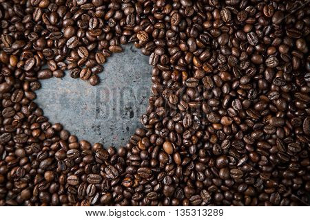 Love coffee Heart from black coffee beans on dark rustic metal grey background copy space frame top view