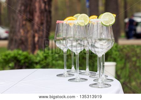 Empty glasses with slices of lime and lemon, decorated sugar standing by the table. Prepared for the lemonade.