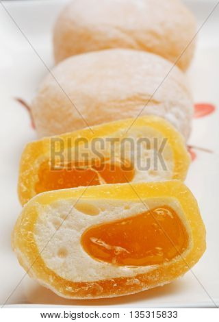 Beautiful japanese fruit mochi rice cakes on white ceramic plate in a cut with delicate mango filling.