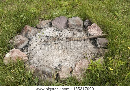 Unlit camp fireplace with ashes and stones on mountain meadow
