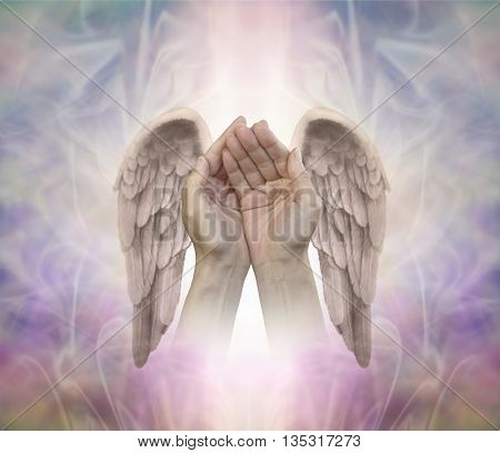 Angelic helping hands - cupped hands with finely detailed Angel wings on either side, on an intricate ethereal patterned background with a central light shaft and copy space