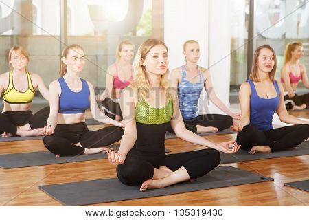 Group of young women in yoga class. Group of people making exercises. Girls do yoga meditation pose, relaxation. Meditation posture. Healthy lifestyle, sport, yoga studio. Fitness club, yoga training