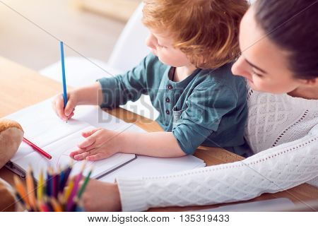 Pleasant time. Young woman passing time with her little son, sitting at the table and watching how he drawing